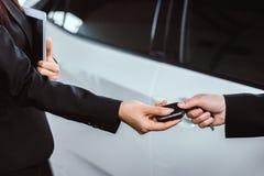 Επιχειρηματίας που παίρνει ένα κλειδί αυτοκινήτων από έναν πωλητή Στοκ Φωτογραφία