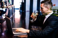 Επιχειρηματίας που παίρνει ένα ποτήρι του κρασιού και που χρησιμοποιεί το lap-top Στοκ φωτογραφίες με δικαίωμα ελεύθερης χρήσης