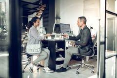 Επιχειρηματίας που παίρνει το βιογραφικό σημείωμα από τη νέα γυναίκα πριν από τη συνέντευξη εργασίας στοκ εικόνα