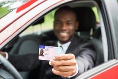 Επιχειρηματίας που παρουσιάζει άδεια οδήγησής του από το ανοικτό παράθυρο αυτοκινήτων στοκ φωτογραφίες