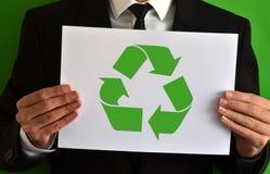 Επιχειρηματίας που παρουσιάζει ένα φύλλο με το σύμβολο ανακύκλωσης Στοκ Εικόνες
