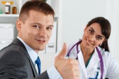Επιχειρηματίας που παρουσιάζει αντίχειρα με το γιατρό Στοκ Φωτογραφίες