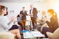 Επιχειρηματίας που παρουσιάζει ενώ συνάδελφοι που επιδοκιμάζουν στο Ο Στοκ εικόνα με δικαίωμα ελεύθερης χρήσης