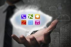 Επιχειρηματίας που παρουσιάζει ζωηρόχρωμα app εικονίδια στο σύννεφο με τα doodles wal Στοκ φωτογραφία με δικαίωμα ελεύθερης χρήσης