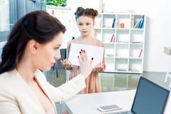 Επιχειρηματίας που παρουσιάζει σημάδι στάσεων στην κόρη της με το λεύκωμα σχεδίων στην αρχή Στοκ φωτογραφία με δικαίωμα ελεύθερης χρήσης