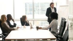 Επιχειρηματίας που παρουσιάζει στην πολυ-εθνική ομάδα πελατών στη συνεδρίαση των γραφείων απόθεμα βίντεο