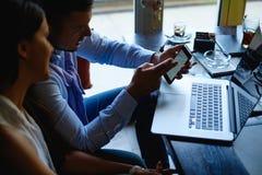 Επιχειρηματίας που παρουσιάζει τηλέφωνο στη γυναίκα συνάδελφός του στοκ φωτογραφίες