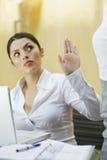 Επιχειρηματίας που παρουσιάζει χειρονομία στάσεων στο συνάδελφό της Στοκ Εικόνα