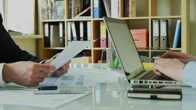 Επιχειρηματίας που παρουσιάζει χρηματοοικονομικά αποτελέσματα στο συνεργάτη του στο σύγχρονο γραφείο 4K