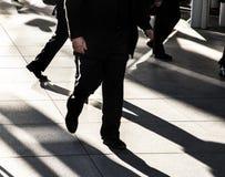 Επιχειρηματίας που περπατά γρήγορα στο πεζοδρόμιο πόλεων που φορά το μαύρο κοστούμι που σκιαγραφείται στον ήλιο με τις μακροχρόνι Στοκ Εικόνες