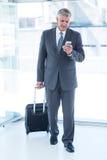 Επιχειρηματίας που περπατά με τις αποσκευές και που χρησιμοποιεί το smartphone του Στοκ Εικόνα