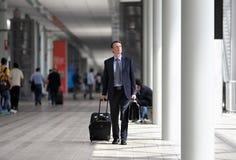 Επιχειρηματίας που περπατά με το καροτσάκι μέσω του πλήθους σε ένα επιχειρησιακό ταξίδι Στοκ Φωτογραφίες