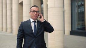Επιχειρηματίας που περπατά στην οδό και που μιλά στο τηλέφωνο φιλμ μικρού μήκους