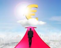 Επιχειρηματίας που περπατά στο βέλος που πηγαίνει προς το ευρο- σύμβολο Στοκ Φωτογραφίες