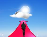 Επιχειρηματίας που περπατά στο βέλος που πηγαίνει πρός τα πάνω προς τη λάμπα φωτός Στοκ φωτογραφία με δικαίωμα ελεύθερης χρήσης