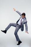 Επιχειρηματίας που πετά πέρα από το γκρίζο υπόβαθρο Στοκ φωτογραφίες με δικαίωμα ελεύθερης χρήσης