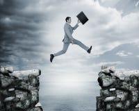 Επιχειρηματίας που πηδά ένα χάσμα μεταξύ των απότομων βράχων Στοκ Εικόνες