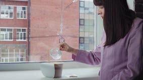 Επιχειρηματίας που προετοιμάζει τα στιγμιαία νουντλς στο παράθυρο ενάντια σε ένα κτήριο τούβλου απόθεμα βίντεο