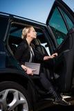 Επιχειρηματίας που προσγειώνει από το αυτοκίνητο στοκ φωτογραφίες