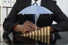 Επιχειρηματίας που προστατεύει τα νομίσματα με την ομπρέλα Στοκ εικόνα με δικαίωμα ελεύθερης χρήσης