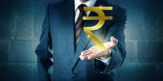 Επιχειρηματίας που προσφέρει ένα χρυσό ινδικό σύμβολο ρουπίων Στοκ Φωτογραφία