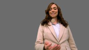 Επιχειρηματίας που ρίχνει ένα νόμισμα στον αέρα στην γκρίζα οθόνη απόθεμα βίντεο