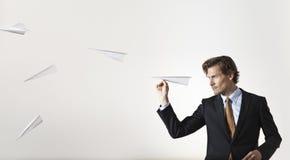 Επιχειρηματίας που ρίχνει τα αεροπλάνα εγγράφου στο στόχο Στοκ Εικόνα