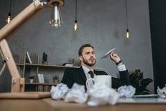 Επιχειρηματίας που ρίχνει το αεροπλάνο εγγράφου καθμένος στον εργασιακό χώρο στοκ φωτογραφία