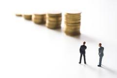 Επιχειρηματίας που σκέφτεται μπροστά από τα νομίσματα Στοκ Φωτογραφία