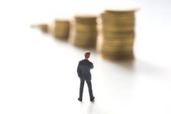 Επιχειρηματίας που σκέφτεται μπροστά από τα νομίσματα Στοκ φωτογραφία με δικαίωμα ελεύθερης χρήσης