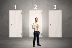 Επιχειρηματίας που σκέφτεται μπροστά από τρεις πόρτες Στοκ Εικόνες