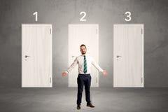 Επιχειρηματίας που σκέφτεται μπροστά από τρεις πόρτες Στοκ Εικόνα