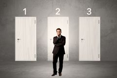 Επιχειρηματίας που σκέφτεται μπροστά από τρεις πόρτες Στοκ Φωτογραφίες