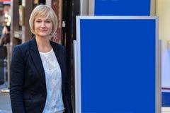 Επιχειρηματίας που στέκεται δίπλα στον πίνακα κτυπήματος Στοκ Εικόνες