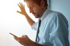 Επιχειρηματίας που στέκεται δίπλα στο παράθυρο γραφείων και που χρησιμοποιεί το smartphone Στοκ Εικόνα