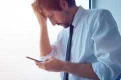 Επιχειρηματίας που στέκεται δίπλα στο παράθυρο γραφείων και που χρησιμοποιεί το smartphone Στοκ φωτογραφίες με δικαίωμα ελεύθερης χρήσης