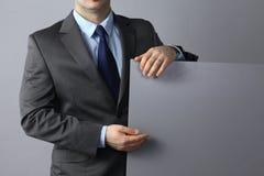 Επιχειρηματίας που στέκεται και που κρατά έναν κενό πίνακα Στοκ εικόνες με δικαίωμα ελεύθερης χρήσης