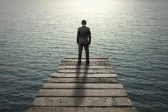 Επιχειρηματίας που στέκεται και που σκέφτεται στην παλαιά ξύλινη αποβάθρα στη θάλασσα Στοκ Εικόνες