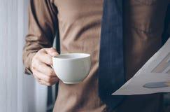Επιχειρηματίας που στέκεται κοντά στον εκλεκτής ποιότητας τόνο φύλλων καφέ και εγγράφου εκμετάλλευσης παραθύρων Στοκ φωτογραφία με δικαίωμα ελεύθερης χρήσης