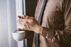 Επιχειρηματίας που στέκεται κοντά στο παράθυρο και που χρησιμοποιεί το τηλέφωνο κυττάρων και που κρατά τον καφέ εκλεκτής ποιότητα Στοκ Εικόνα