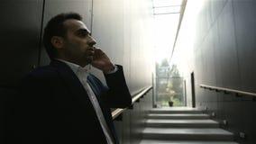 Επιχειρηματίας που στέκεται μέσα στο κτήριο και που μιλά με κινητό τηλέφωνο απόθεμα βίντεο