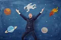 Επιχειρηματίας που στέκεται με τα όπλα του επάνω και τα διαστημικά σκίτσα πίσω από τον στο μπλε υπόβαθρο πινάκων κιμωλίας Στοκ εικόνα με δικαίωμα ελεύθερης χρήσης