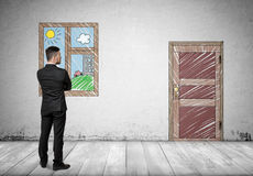 Επιχειρηματίας που στέκεται μπροστά από το παράθυρο που εξετάζει την πόρτα Στοκ εικόνα με δικαίωμα ελεύθερης χρήσης