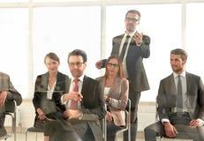 Επιχειρηματίας που στέκεται να απευθυνθεί στους συναδέλφους στη συνεδρίαση στοκ φωτογραφίες