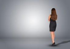 Επιχειρηματίας που στέκεται σε ένα κενό γκρίζο δωμάτιο rear Στοκ εικόνα με δικαίωμα ελεύθερης χρήσης