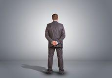 Επιχειρηματίας που στέκεται σε ένα κενό γκρίζο δωμάτιο rear Στοκ Φωτογραφίες