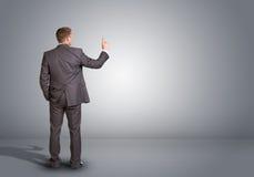 Επιχειρηματίας που στέκεται σε ένα κενό γκρίζο δωμάτιο rear Στοκ φωτογραφία με δικαίωμα ελεύθερης χρήσης