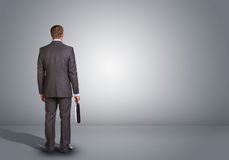 Επιχειρηματίας που στέκεται σε ένα κενό γκρίζο δωμάτιο rear Στοκ εικόνες με δικαίωμα ελεύθερης χρήσης