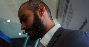 Επιχειρηματίας που στέκεται σε μια κυλιόμενη σκάλα απόθεμα βίντεο