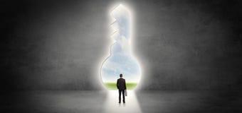 Επιχειρηματίας που στέκεται σε μια μεγάλη κλειδαρότρυπα στοκ εικόνες